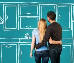 Happy embracing couple planning their home kitchen furnishing.